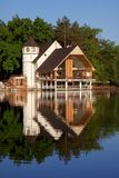Forest home at the lake. Day light Stock Image
