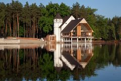 Forest home at the lake. Day light Royalty Free Stock Image