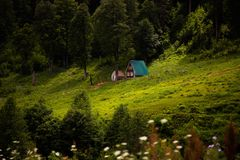 Forest house in the mountains. Beautiful view of a forest house high in the mountains. Green lawn in the mountains. Hermit`s life in the forest. Forest landscape Stock Photography