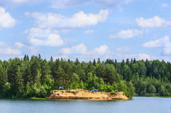 Forest lake with clear water and the island on which rest the tourists and travelers, natural landscape blue sky Stock Images
