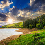 Forest and lake near the mountain at sunset Stock Photography
