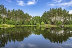 Forest lake with reflection in water. Summer place with arbor for fishing and relax Stock Image