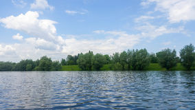 Forest lake under blue cloudy sky Royalty Free Stock Photography