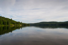 Forest lake under blue cloudy sky. Beautiful forest lake under blue cloudy sky on summer day Stock Photography