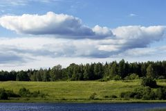 Forest landscape. Forest view against blue cloudy sky with lake on foreground Stock Photography