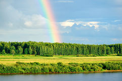 Forest landscape - birds eye view of colorful forest and river under rainbow and dramatic sky Royalty Free Stock Photos