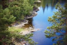 Forest landscape and lake with clear water, covered with ripples stock photos