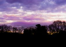 Forest landscape with pink and purple nacreous clouds, a colorful sky effect that rarely occurs in winter stock photography