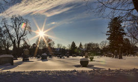 Forest Lawn Cemetery. Wide angle view of snow covered graves in a Cemetery. Image is shot looking into the sun using only a UV filter stock images