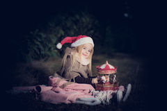 In forest with light 2. 2-3 years old little girl in forest with candle and christmas staff Stock Photo
