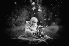 In forest with light. 2-3 years old little girl in forest with candle and christmas staff Stock Photo
