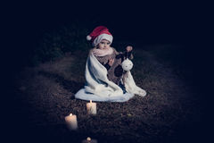 In forest with light 2. 2-3 years old little girl in forest with candle and christmas staff Royalty Free Stock Image
