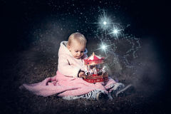 In forest with light. 2-3 years old little girl in forest with candle and christmas staff Stock Image