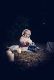 In forest with light. 2-3 years old little girl in forest with candle and christmas staff Royalty Free Stock Photos