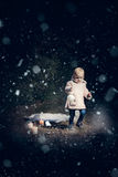 In forest with light. 2-3 years old little girl in forest with candle and christmas staff Royalty Free Stock Images