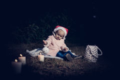 In forest with light. 2-3 years old little girl in forest with candle and christmas staff Royalty Free Stock Image