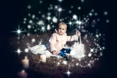 In forest with light. 2-3 years old little girl in forest with candle and christmas staff Stock Images