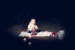 In forest with light. 2-3 years old little girl in forest with candle and christmas staff Stock Photos