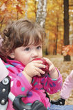 In the forest a little girl eats red apple Stock Image