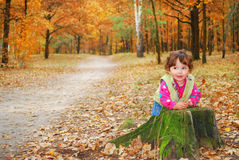 In the forest little girl playing near the stump. Royalty Free Stock Image
