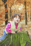 In the forest little girl playing near the stump. Stock Image