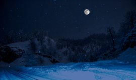 forest on a meadow full of snow in high mountains with snowy tops at night in full moon light. Azerbaijan. Lerik Stock Images