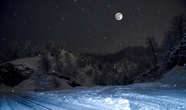 forest on a meadow full of snow in high mountains with snowy tops at night in full moon light. Azerbaijan. Lerik Stock Photo