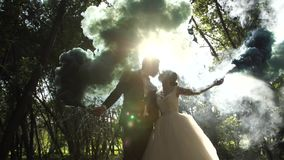 Forest In the mist. The lovers kissing in sun rays. The lovers kiss in the sun. They keep smoke bombs and the smoke obscures them from the rays. A very stock video
