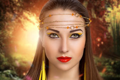 Forest nymph. Young beautiful woman model lady woman warrior fairy tale character. Background forest dawn nature. Bright makeup, expressive eyes, Cleopatra style Stock Photography