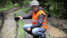 Forest officer filmed with tablet PC rutted forest road stock footage