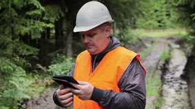 Forest officer with tablet PC on rutted forest road stock footage