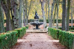 Forest path in Autumn in Aranjuez. Path inside a forest in Aranjuez in Autumn, Madrid, with leaves covering the ground and the Fuente de Baco ca. 1656 fountain Stock Images
