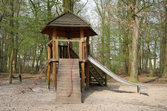 Forest playground with wooden hut and slide Royalty Free Stock Images