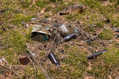 Forest pollution with garbage plastic bottles, glass bottles, metal cans royalty free stock photo
