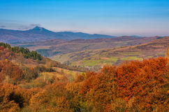 Forest with red foliage on hills in countryside. Forest with red foliage on hills in autumnal countryside. stunning view of mountainous area with gorgeous high Stock Image
