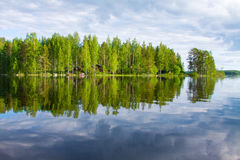 Forest with red house on the lake shore, sky with clouds reflect Royalty Free Stock Image