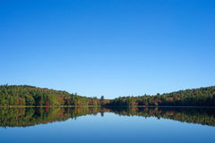 Forest reflection on calm water of a lake. The reflection of a forest on Sanborn Pond in Morrill Maine with blue sky and fall foliage Stock Photography
