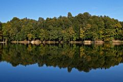 Forest reflection in lake. Lake waters near Trakoscan castle, Croatia. Early autumn and reflection of the lakeside forest trees in the calm water Stock Photo