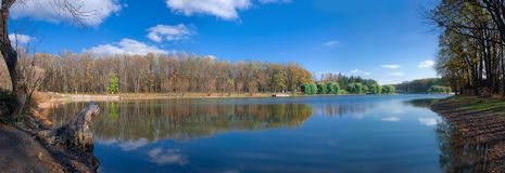 Forest reflection panorama. Panorama of forest reflection in limpid lake at autumn sunny day Stock Photos