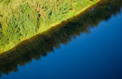 Forest reflections on big lake Royalty Free Stock Photos