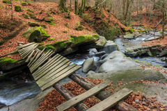Forest river with old bridge. Old broken bridge of planks over the river with stones and moss in the forest near the mountain slope Stock Image