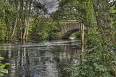 Forest river with an old stone bridge  in HDR Stock Photos