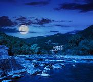 Forest river with stones and bridge. Mountain river with stones in the forest near the metal bridge at night in  full moon light Royalty Free Stock Photos