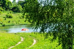 Forest road on lake with view red umbrella.  royalty free stock photo