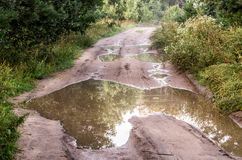 Forest road with puddles. Difficult driving circumstances stock photography