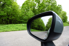 Forest road reflection,  rearview car driving mirror view green. Forest road Stock Image