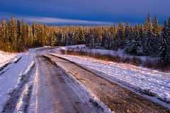 Forest road in winter. Snow covered road through forest in winter with late evening light stock photo