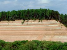 Forest rock 1. A cliff with a forest and visible ground layers near the Opoki village, northern Russia. Geology concepts Stock Photos