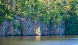 Coastal rocks with forest bathed in the sun. Tilt-Shift effect. The forest on the rocks of the river is lit by the rays of the sun. Tilt-Shift effect royalty free stock photography