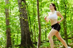 Forest Runner. Beautiful young woman runner in a green forest royalty free stock photography